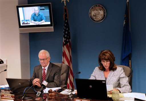 O.J. Simpson, in custody at the Lovelock Correctional Center, is on the video screen above Nevada Board of Parole hearing representative Robin Bates, left, and Commissioner Susan Jackson during a video conference parole hearing on July 25. (AP)