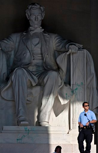 A U.S. Park Police officer stands guard next to the statue of Abraham Lincoln at the memorial in Washington, Friday, July 26, 2013, after the memorial was closed to visitors after someone splattered green paint on the statue and the floor area.