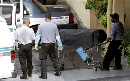 Miami-Dade morgue workers carry out a body out at the scene of a fatal shooting in Hialeah, Fla., Saturday, July 27, 2013. (AP Photo/Alan Diaz)