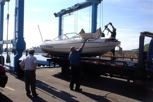 Officials remove the 21-foot Stingray powerboat involved in an accident on the Hudson River from the water in Piermont, N.Y, on Saturday, July 27, 2013.  (AP Photo/The Journal News, Frank Becerra Jr.)