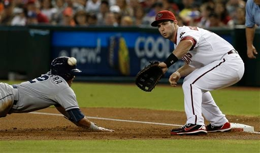 Arizona Diamondbacks' Paul Goldschmidt, right, waits for a throw as San Diego Padres' Everth Cabrera dives safely back to first base in the first inning of a baseball game on Friday, July 26, 2013, in Phoenix. (AP Photo/Ross D. Franklin)