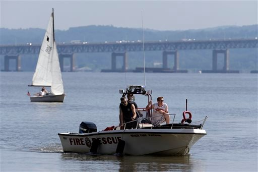 Rescue workers on a boat search the Hudson River south of the Tappan Zee Bridge for two people who went missing following a boat crash in Piermont, N.Y. on Saturday, July 27, 2013.