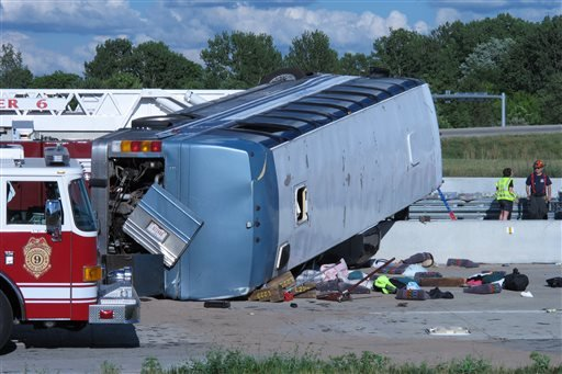 Seat cushions, clothing and other objects line the pavement next to the wreckage of bus that crashed Saturday, July 27, 2013, on Indianapolis' far north side while carrying teenagers returning from a summer camp in Michigan.
