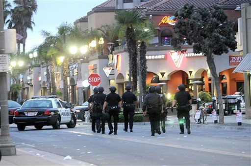 A line of police officers march up MaIn Street in Huntington Beach, Calif. Sunday July 28, 2013. (AP Photo/The Orange County Register,Richard Koehler)