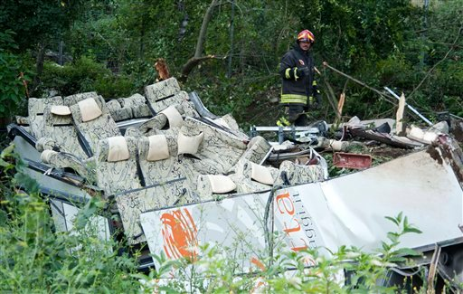 A firefighter looks at the wreckage of a bus which crashed off a highway near Avellino, southern Italy, Monday, July 29, 2013.