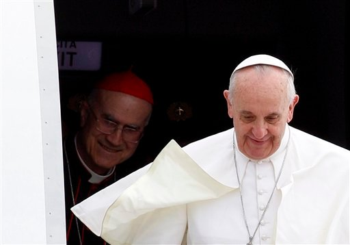 Pope Francis, followed by Vatican Secretary of State Cardinal Tarcisio Bertone, disembarks from the plane after landing from Rio de Janeiro, Brazil, at Ciampino's military airport, on the outskirts of Rome, Monday, July 29, 2013.