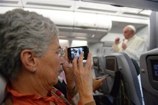 A journalist takes a photo of Pope Francis speaking during a news conference aboard the papal flight on the journey back from Brazil, Monday, July 29, 2013. (AP)