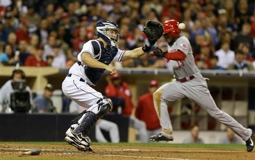 Cincinnati Reds' Derrick Robinson beats the throw and the tag by San Diego Padres catcher Nick Hundley while scoring from third on an infield ground ball in the fifth inning of a baseball game in San Diego, Monday, July 29, 2013. (AP Photo/Lenny Ignelzi)