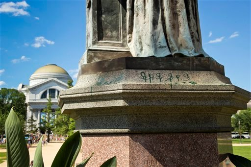 Green paint is seen on the pedestal of the statue of Joseph Henry, outside the headquarters of the Smithsonian Institution on the National Mall in Washington, Monday, July 29, 2013.