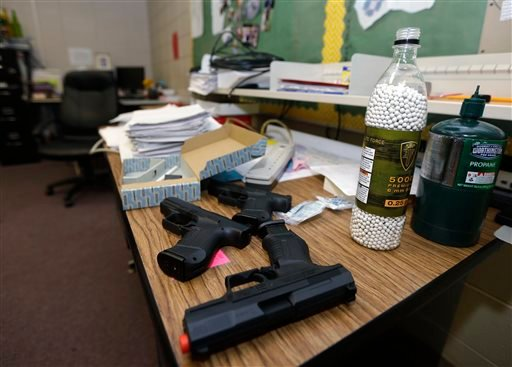 In this photo taken July 11, 2013, practice air-powered handguns sit on a teacher's desk in a classroom at Clarksville High School in Clarksville, Ark.