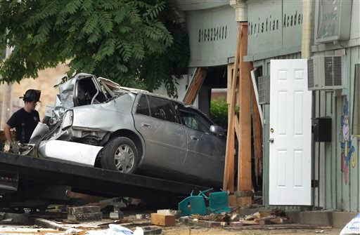 A car is pulled from a day care center after it crashed into the building Tuesday, July 30, 2013, in Kansas City, Mo.(AP)