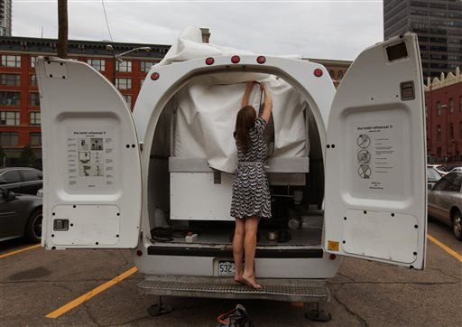 Amelia Langer, an assistant curator of Draft Urbanism, the art exhibition of the 2013 Biennial of the Americas, unzips the opening to a hotel room made of aluminum and inflated vinyl capable of being held aloft by a van-mounted scissor lift.