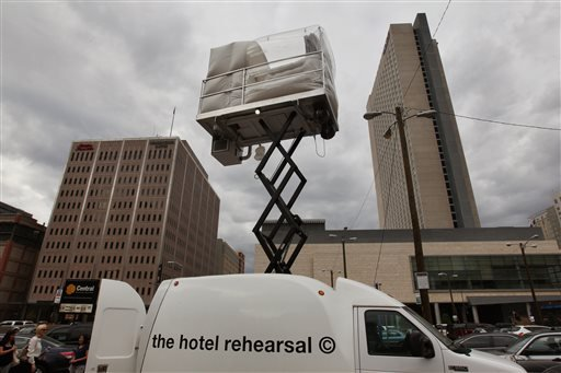 A hotel room made of aluminum and inflated vinyl is held aloft by a van-mounted scissor lift, on promotional display in a parking lot in downtown Denver, Wednesday July 25, 2013.