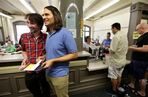 Gary McDowell, left, and Zachary Marcus, both of Providence, R.I., display their newly obtained marriage license at City Hall, in Providence, Thursday, Aug. 1, 2013. (AP Photo/Steven Senne)