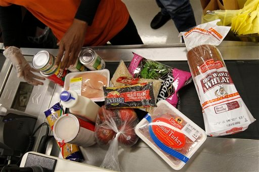 In this April 23, 2012, file photo Philadelphia Mayor Michael Nutter's purchases are scanned by a cashier at a ShopRite grocery story in Philadelphia after Nutter pledged to live on the average food stamp benefit of five dollars a day for the entire week.