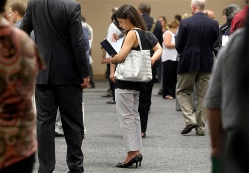 In this Monday, July 15, 2013 file photo, a woman waits to talk with employers at a job fair for laid-off IBM workers in South Burlington, Vt. The government issues the jobs report for July on Friday, Aug. 2, 2013.