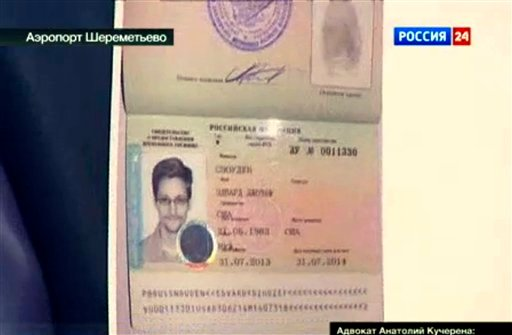 In this image taken form Russia24 TV channel, Russian lawyer Anatoly Kucherena shows Snowden's a temporary document Russia while speaking to the media after visiting National Security Agency leaker Edward Snowden at Sheremetyevo airport outside Moscow.