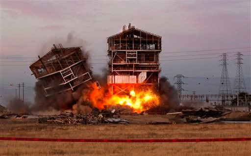 An explosion knocks down one of the remaining towers at the old Kern Power Plant, Saturday, Aug. 3, 2013 in Bakersfield, Calif.