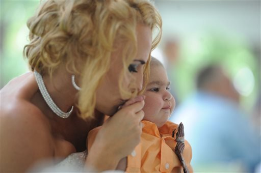 Newlywed Christine Stevenson kisses the hand of her son, Logan Stevenson, 2, after marrying Sean Stevenson in a wedding ceremony on Saturday, Aug. 3, 2013 in Jeannette, Pa.