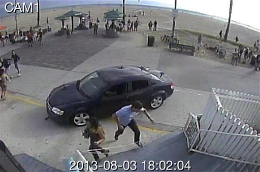 In this still frame made from security camera footage from Snapchat, Inc. headquarters, pedestrians scatter as a car drives through a packed afternoon crowd along the Venice Beach boardwalk in Los Angeles, Saturday, Aug. 3, 2013.