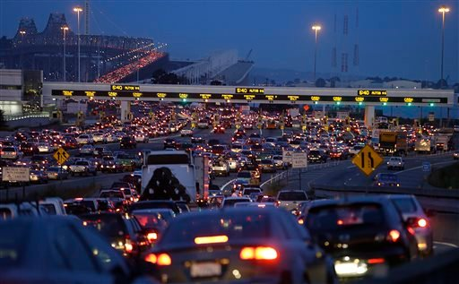 In this file photo from Monday, July 1, 2013, commuters wait in standstill traffic to pay their tolls on the San Francisco-Oakland Bay Bridge in Oakland, Calif.