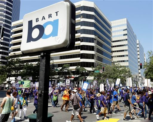 In this file photo from Monday, July 1, 2013, striking Bay Area Rapid Transit workers picket as they close the intersection of 14th & Broadway on Monday, July 1, 2013, in downtown Oakland, Calif.