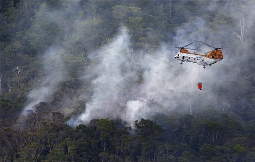 Smoke billows from the crash site of U.S. air force rescue helicopter HH-60 at Camp Hansen as U.S. marine helicopter CH46 flies over to drop water, on the southern island of Okinawa, Japan, Monday, Aug. 5, 2013.