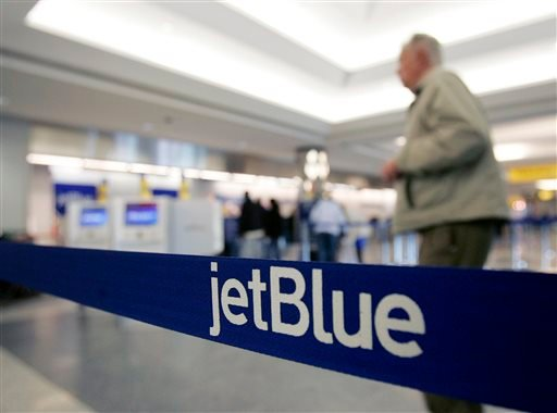 In this Wednesday Feb. 1, 2006, file photo, a pedestrian makes his way to the e-ticket counter of JetBlue at New York's LaGuardia Airport.