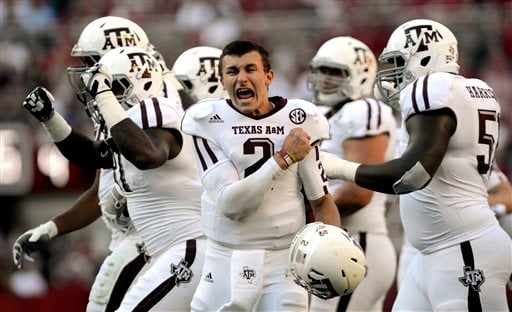 In this Nov. 10, 2012 file photo, Texas A&M quarterback Johnny Manziel (2) celebrates after a review proves an Aggie touchdown during the first half of an NCAA college football game against Alabama in Tuscaloosa, Ala.
