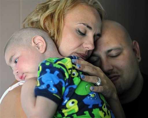 This July 30, 2013 photo, Christine Swidorsky holds her son, Logan Stevenson, 2, with her husband-to-be and Logan's father Sean Stevenson, for a portrait in their Jeannette, Pa., home.