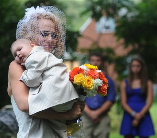 This Aug. 3, 2013 file photo, Christine Swidorsky carries her son and the couple's best man, Logan Stevenson, 2, down the aisle to her husband-to-be Sean Stevenson during the wedding ceremony in Jeannette, Pa.