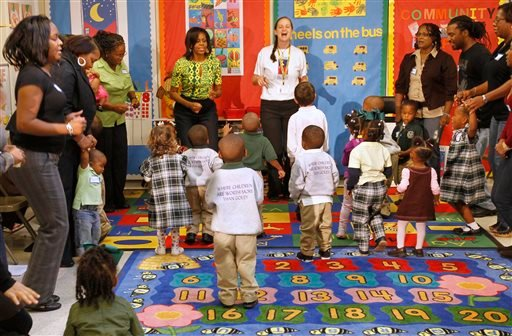 """Nov. 1, 2011 file photo: First Lady Michelle Obama sings and dances to exercises as she visits the Royal Castle Child Development Center, as part of the """"Lets Move!"""" initiative in New Orleans. (AP Photo/Gerald Herbert)"""