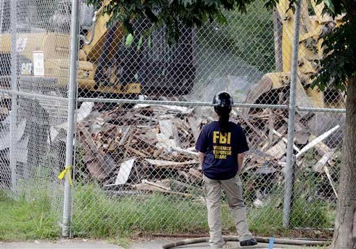 An FBI agent watches as the house where three women were held captive and raped for more than a decade is being demolished Wednesday, Aug. 7, 2013, in Cleveland.