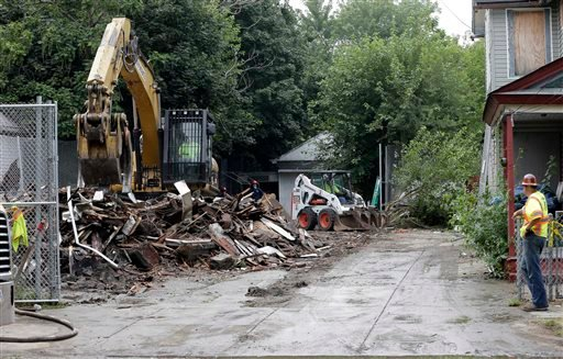 Workers demolish the house where three women were held captive and raped for more than a decade, Wednesday, Aug. 7, 2013, in Cleveland.