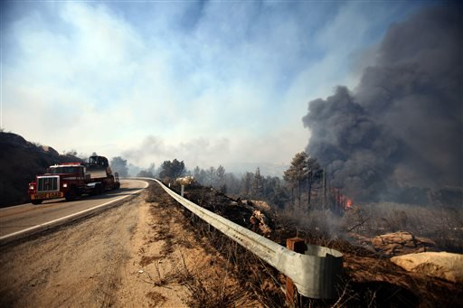 The wildfire burns along State Route 243 as a truck carrying a Cal Fire bulldozer moves up the road on Wednesday, Aug. 7, 2013. (AP Photo/The Desert Sun, Richard Lui) (Richard Lui The Desert Sun)
