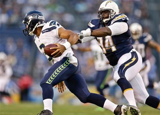 Seattle Seahawks quarterback Russell Wilson escapes the grasp of San Diego Chargers defensive end Corey Liuget.