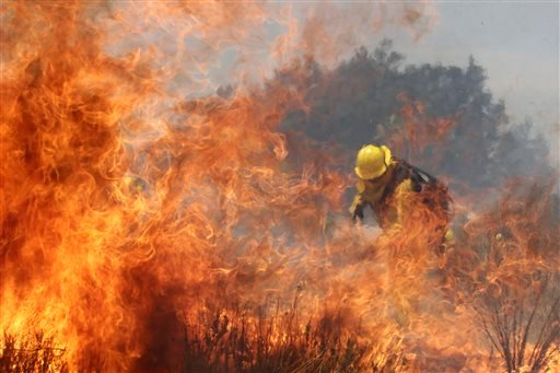A firefighter battles a wildfire on Thursday, Aug. 8, 2013, in Cabazon, Calif. (AP Photo/Jae C. Hong)