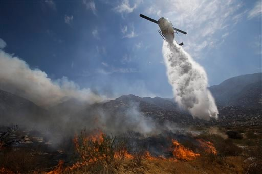 A helicopter drops water over a wildfire on Thursday, Aug. 8, 2013, in Cabazon, Calif. (AP Photo/Jae C. Hong)