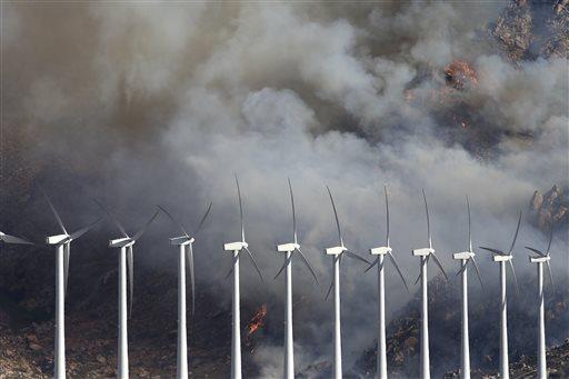 A wildfire burns near wind turbines on Thursday, Aug. 8, 2013, near Cabazon, Calif. (AP Photo/Jae C. Hong)