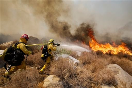 Firefighters battle a wildfire, Thursday, Aug. 8, 2013, in Cabazon, Calif. (AP Photo/Jae C. Hong)