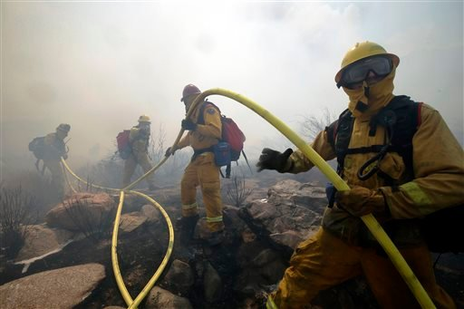 Firefighters carry a hose while battling a wildfire on Thursday, Aug. 8, 2013, in Cabazon, Calif. (AP Photo/Jae C. Hong)