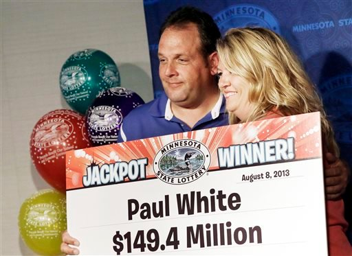 Paul White, of Ham Lake, Minn. and his girlfriend Kim VanReese, hold up the winnings about his plans after he was announced one of the winners of the $448.4 million Powerball Jackpot, Thursday, Aug. 8, 2013 in Minneapolis. (AP Photo/Jim Mone)