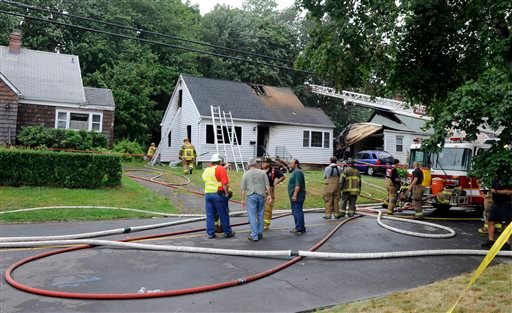 Firefighters work the scene of a plane crash, Friday, Aug. 9, 2013, in East Haven, Conn. The multi-engine, propeller-driven plane plunged into a working-class suburban neighborhood near Tweed New Haven Airport, on Friday. (AP Photo/Fred Beckham)
