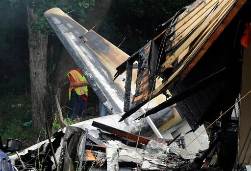 A responder surveys the scene of a small plane crash, Friday, Aug. 9, 2013, in East Haven, Conn.