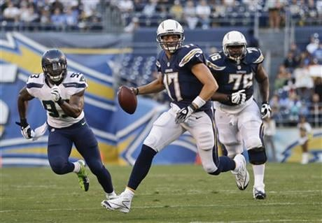 San Diego Chargers quarterback Philip Rivers scrambles away from Seattle Seahawks linebacker O'Brien Schofield in the first quarter of an NFL preseason football game Thursday, Aug. 8, 2013, in San Diego.