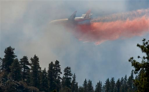 Tanker 911, operated by 10 Tanker Air Carrier drops retardant over the Sharp Fire, Friday, Aug. 9, 2013 in Wrigthwood Calif.