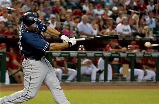 San Diego Padres' Carlos Quentin connects for an RBI single against the Arizona Diamondbacks in the first inning of a baseball game on Sunday, July 28, 2013, in Phoenix. (AP Photo/Ross D. Franklin)