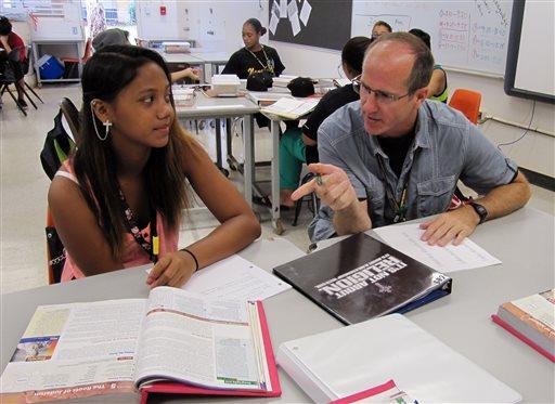 Dennis Tynan, right, talks to 9th grader Chyda Iokua during a 9th grade social studies class at Nakakuli High and Intermediate School in Waianae, Hawaii on Friday, Aug. 9, 2013.