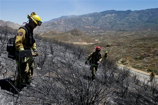 Firefighters look for hot spots as they walk through the scorched area on Friday, Aug. 9, 2013, near Banning, Calif. Southern California firefighters are facing another day of battle as they try to corral a wildfire that has destroyed 26 homes.