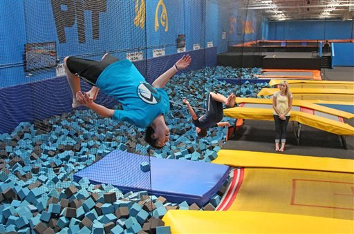In this July 31, 2013, photo, Hunter Gottfredson, left, 15, of Elk Ridge, flips at the Get Air Hang Time indoor trampoline park in Orem, Utah.